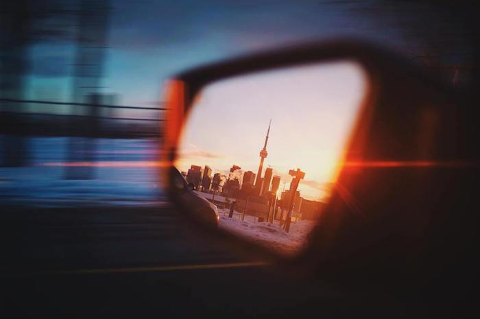 Side view mirror on car reflecting Toronto skyline